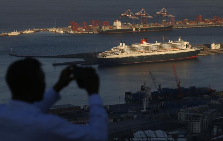 A visitor takes photographs of Cunard's cruise liner Queen Mary 2 as the ship sits berthed in Cape Town harbour in this picture taken January 27, 2014.